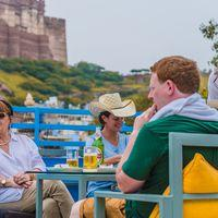 Travellers enjoying drinks at our rooftop cafe overlooking the Mehrangarh Fort.