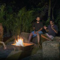 Backpackers sharing travel stories over a bonfire at Zostel